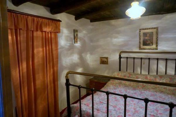 Dormitorio rústico con cama antigua de forja