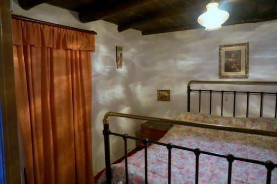Dormitorio rústico con cama de forja