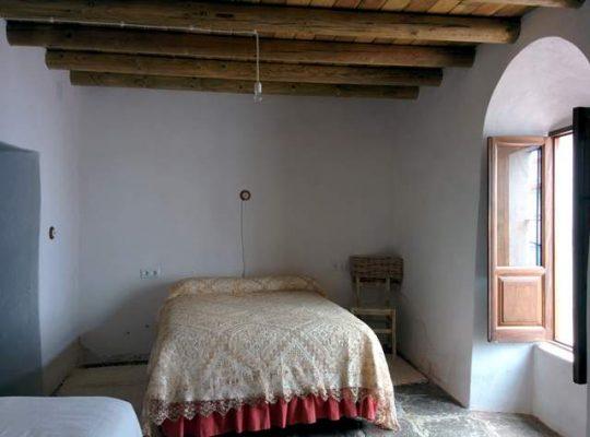 Dormitorio antiguo con anchos muros encalados